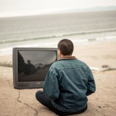 man meditating on beach in front of an unplugged tv